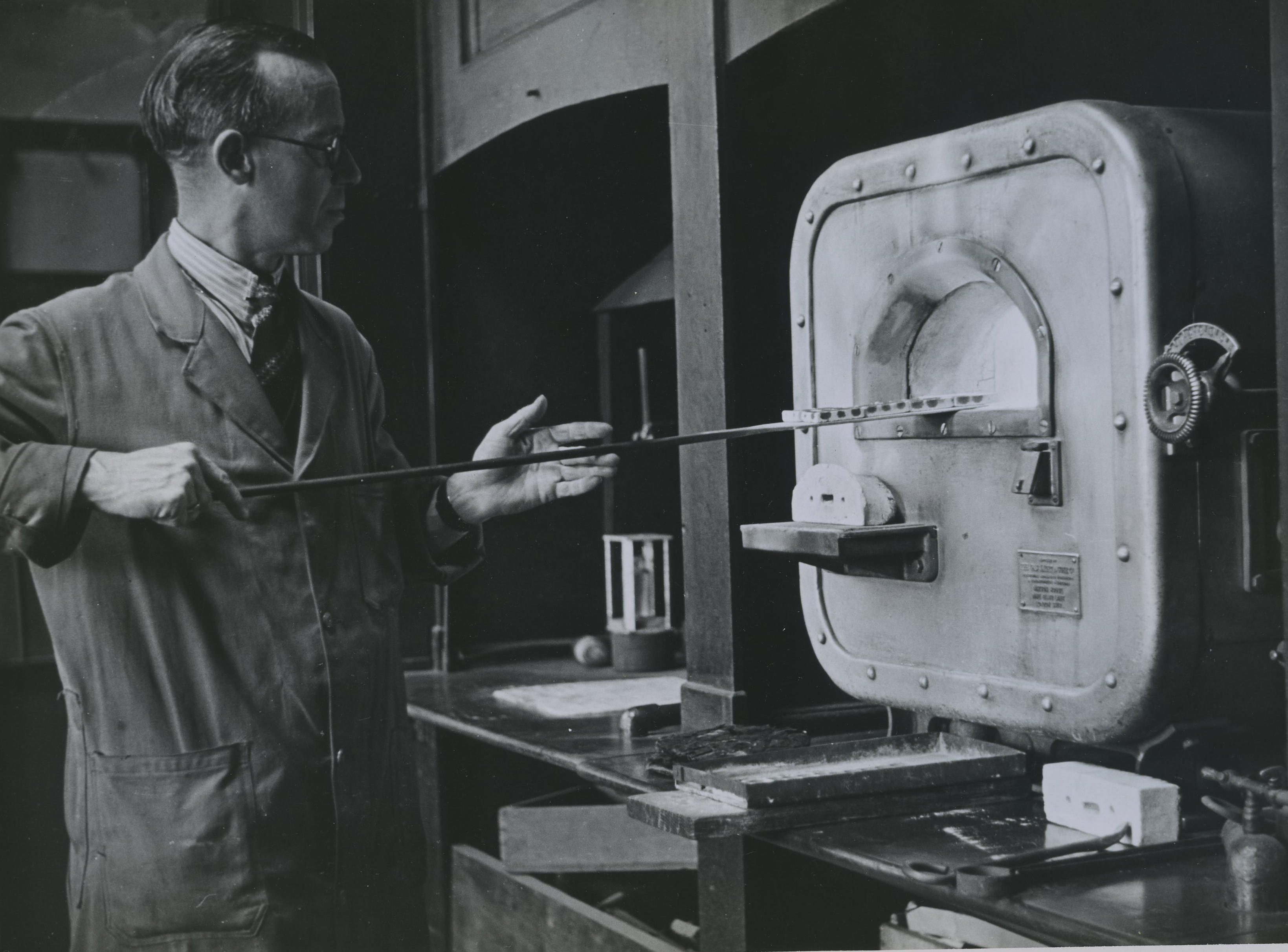 Laboratory - cupels being placed inside the furnace circa 1960