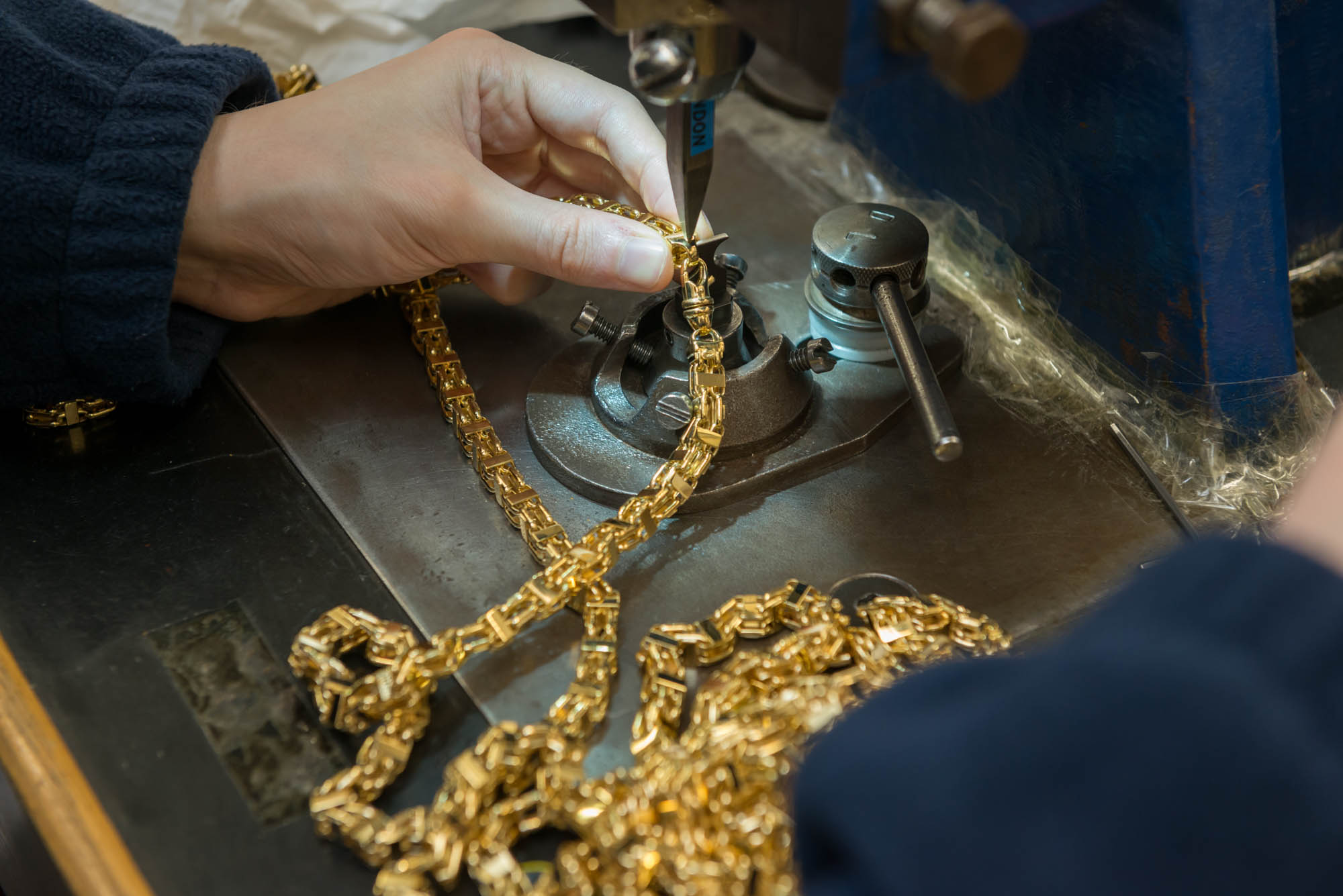 Gold chain being marked on fly press